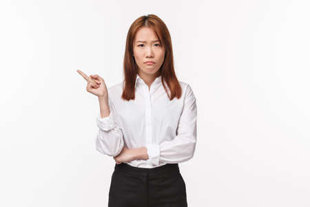Portrait of upset and distressed asian female entrepreneur, sulking disappointed pointing finger left at something bad, feel let down and disturbed, standing unamused white background