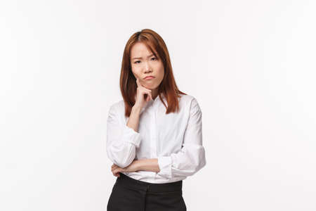 Thoughtful and serious grumpy young asian woman thinking, having troubles with making-up plan, lean on hand frowning and staring annoyed camera, standing offended or distressed