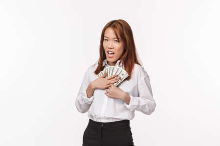 Greedy young rich asian female in white shirt, press money to chest and squinting suspicious, scheming, stole cash, saving for future vacation, standing white background needy