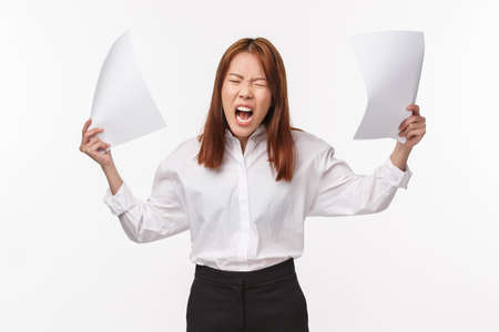 Career, business and women concept. Portrait of distressed and annoyed aggressive young asian woman screaming pissed-off and angry, throwing documents, being outraged, white background Stockfoto