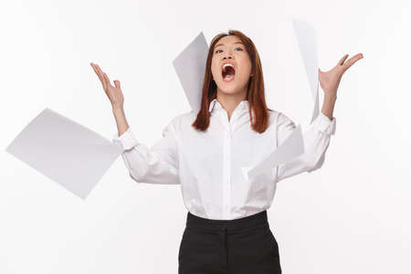 Career, business and women concept. Portrait of angry young office lady losing temper, being pissed-off throwing papers and screaming pressured, feel pissed shouting in anger, white background