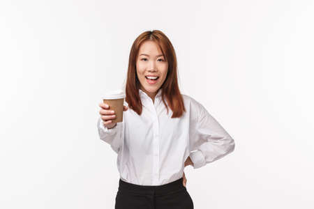 Office work, people and business concept. Energized cheerful asian woman suggest drink, give you cup of coffee and smiling say here you are, treating friend in cafe, standing white background Archivio Fotografico