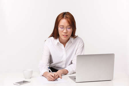 Career, work and women entrepreneurs concept. Close-up portrait busy hardworking asian businesswoman, office lady sitting at desk with laptop, writing down notes, prepare report for boss