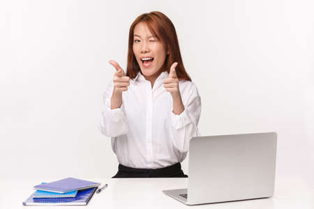 Career, work and women entrepreneurs concept. Close-up portrait of cheeky excited asian office lady assure all good, encourage you visit her company and use service, sit with laptop and notebook