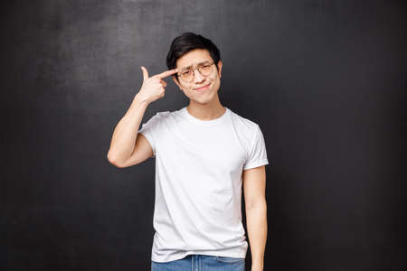 Just shoot me already. Bothered and annoyed asian young guy grimacing upset and irritated, make finger gun pistol near foreahead at if kill himself, tired listening to stupid conversation Stock Photo