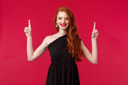 Celebration, events, fashion concept. Portrait of confident charming redhead female in elegant black dress, evening makeup, showing good store for buying prom outfit, pointing fingers up, smile Reklamní fotografie