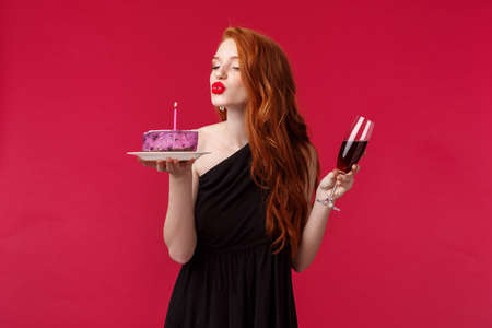 Portrait of elegant good-looking feminine redhead woman with red lipstick, evening makeup and black dress, celebrating birthday at party with red wine and b-day cake, blowing candle sensually