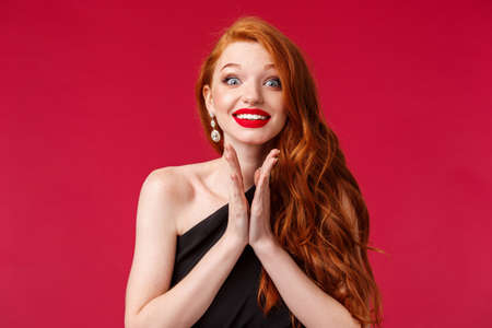 Close-up portrait of excited and eager young gorgeous redhead woman clap hands anticipating performance, smiling hopeful, awaiting for artist come on stage cant wait to hear him, red background
