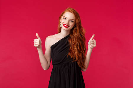 Fashion, luxury and beauty concept. Portrait of charming supportive young redhead woman in black elegant dress, makeup, smiling pleased show thumbs-up in approval or like, red background Reklamní fotografie
