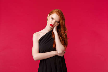 Portrait of annoyed and bored reluctant young redhead female in black evening dress, tired of people, boring party or prom night, lean on palm look camera gloomy, stand red background Stock Photo