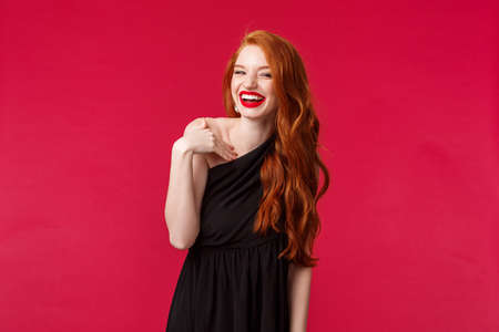 Portrait of elegant coquettish redhead woman in black dress and evening makeup, laughing silly at camera, gesturing as if talking to person during formal event, stand red background