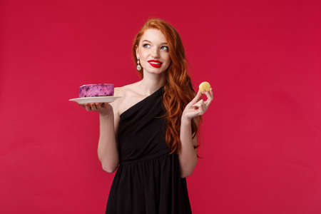 Thoughtful and dreamy gorgeous slim redhead woman in black dress thinking about eating dessert while taking care of her body, look away pondering and smiling, hold cookie and cake