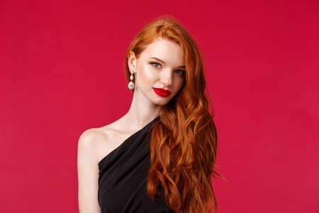 Close-up portrait of attractive sensual and flirty young woman with red lipstick, capturing gaze, wear earrings and black dress, look camera sassy knows what she wants, red background