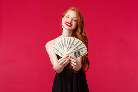 Luxury, beauty and money concept. Portrait of gorgeous sensual young redhead woman in black dress congratulate lucky winner with prize, giving dollars cash reward, smiling camera, red background Reklamní fotografie