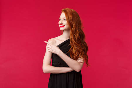 Celebration, events, fashion concept. Satisfied, charming redhead woman with red lipstick, wear black elegant dress, pointing and looking left with happy pleased expression, black background