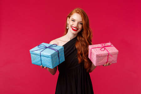 Celebration, holidays and women concept. Portrait of elegant gorgeous young redhead woman in black party dress, holding two gifts in blue and pink boxes, smiling camera cheerful, red background