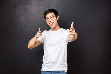 Your rock man. Cheerful handsome young asian guy attend awesome party praise nice work, pointing at camera, recruiting person join his team, smiling happy, black background