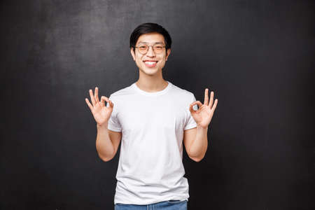 Everything be good, I guarantee. Relaxed happy smiling young asian man showing okay signs as assure all done great, work went well, rating excellent product, guarantee quality 版權商用圖片