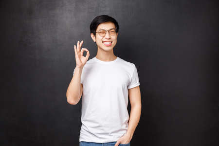 Carefree happy smiling young asian guy left satisfied after trying new product, visit company and use their good services, show okay sign and wink joyfully, pleased over black background 版權商用圖片