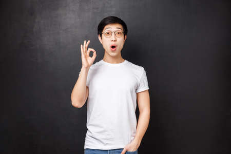 Amazed and enthusiastic young surprised asian guy left speechless and impressed after seeing premier of new movie, show okay sign look astounded standing black background