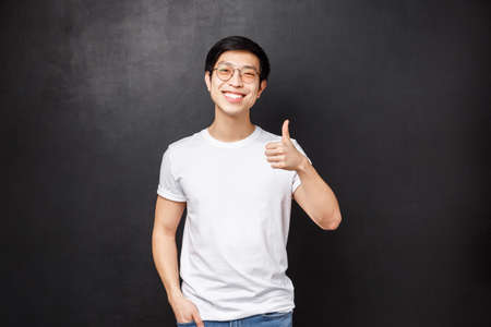 Lifestyle and people concept. Handsome young asian man in white t-shirt, sunglasses standing over black background show thumb-up and nod in agreement, smiling satisfied, leave positive feedback