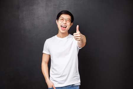 Lifestyle and people concept. Happy and satisfied young asian modern guy customer left impressed and pleased after attending awesome concert, show thumb-up in approval and wink joyfully