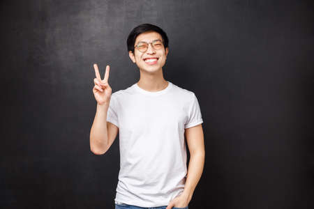 Lifestyle and people concept. Happy positive asian guy with beaming white smile showing peace sign, enjoying having fun and feel entertained, visit team building courses, leave positive review