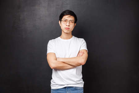Portrait of confident serious-looking asian macho man in glasses, squinting cautious and looking camera disbelief, cross hands over chest, do not trust person talking to, black background