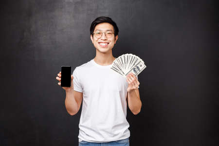 Portrait of proud rich young man showing dollars, fan of money and mobile phone display, smiling as bragging where he won receive prize cash, standing satisfied over black background Standard-Bild