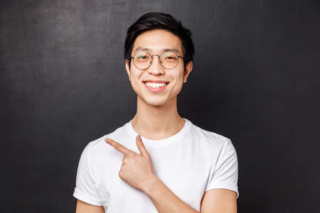 Close-up portrait of cheerful young adult guy start own business on internet platform, wearing glasses, pointing finger left and smiling, give recommendation, suggest visit webpage Stockfoto
