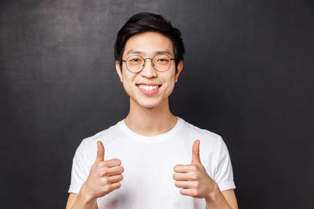 Close-up portrait of satisfied, confident asian young man in white t-shirt, show thumbs-up in approval, smiling guarantee good product, recommend service or company, black background 版權商用圖片