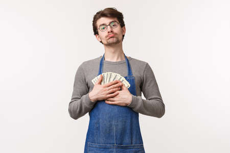 Small business, finance and career concept. Portrait of cute greedy young man dont want to waste money, hugging cash and pouting as need to pay rent, saved salary for new computer, white background Stock Photo