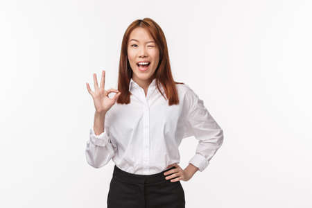 Unbothered cheerful pretty asian woman in white shirt, show okay gesture, confirm work done, wink and smiling happy, assure all good, everything perfect, excellent job, white background 版權商用圖片