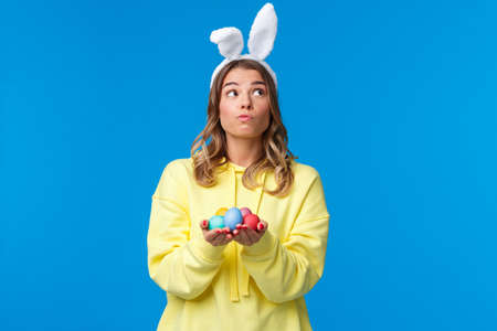 Thoughtful cute caucasian girl in rabbit ears thinking, looking up pondering and dreamy, holding Easter eggs, decide where hide it during traditional holiday game, blue background 免版税图像