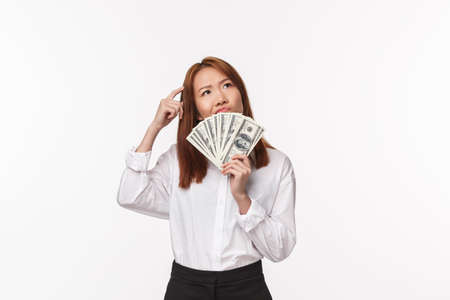 Portrait of indecisive and thoughtful young successful asian woman earn money and dont know how invest them, scratching head uncertain smirk pondering, holding fan of cash, white background
