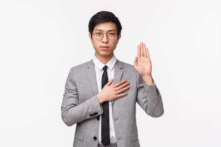 Waist-up portrait of devoted good-looking asian young man in grey suit, making promise, pledge or give oath, raise one hand and put palm on hear as being honest and sincere, white background