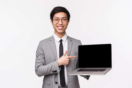 Waist-up portrait of professional, smart handsome businessman, asian guy in suit holding computer, pointing at laptop screen and smiling as introduce program or company project, white background
