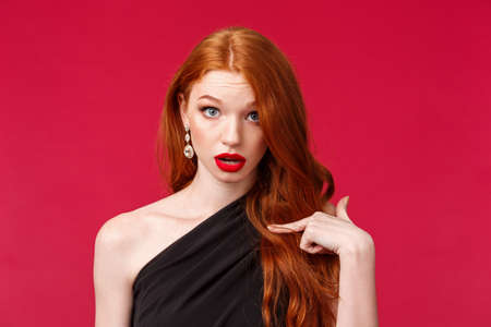 Who, me. Shocked and surprised startled redhead girl in black dress look questioned and confused, stare disbelief as pointing at herself, being picked or accused in something, red background Standard-Bild