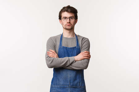Serious-looking skeptical male manager looking at employees watching how they work, grumpy staring camera cross hands over chest, being disappointed or reluctant, stand in apron at coffee shop