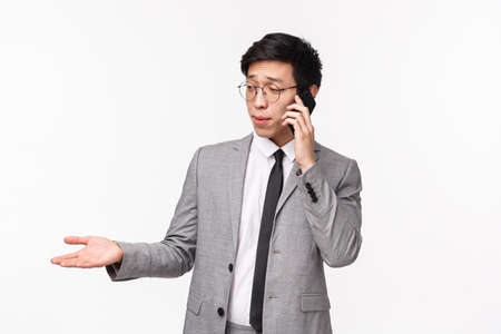 Waist-up portrait of serious-looking skeptical young asian businessman give consultation on phone, having important call from client, talking on smartphone, gesturing hand and grimace indecisive