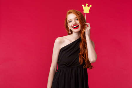 Show them who is queen. Adorable redhead caucasian woman in luxurious black dress, red lipstick, holding crown on stick and smiling, having fun with girlfriends night out, red background Reklamní fotografie