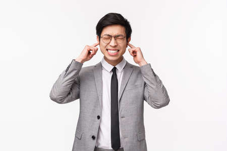 Waist-up portrait of annoyed and tensed asian businessman, office manager close eyes and clench teeth from discomfort, shut ears as hear annoying loud sound, bothered by noise, white background