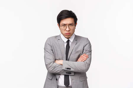 Waist-up portrait of offended and defensive young moody asian male office manager, clerk being upset with coworker prank, cross hands chest and look judgemental camera with pissed-off face