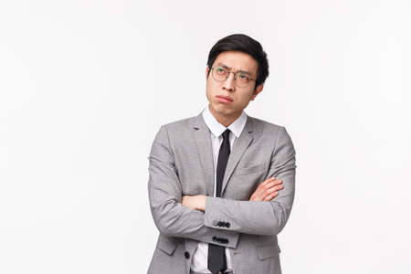 Waist-up portrait of puzzled, serious-looking asian guy in grey suit, looking up frowning and squinting thoughtful, cross hands chest, trying make-up solution, making choice indecisive