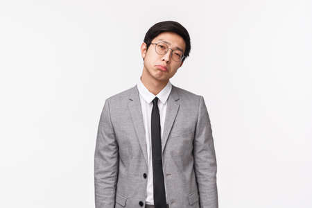 Waist-up portrait of gloomy and reluctant, unimpressed bored asian man in suit, businessman pulling unsatisfied grimace, looking judgemental and skeptical camera, standing white background
