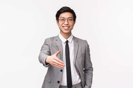 Waist-up portrait of friendly confident, successful asian businessman stretching hand forward for handshake with business partner, nice to meet you, formal greeting, white background