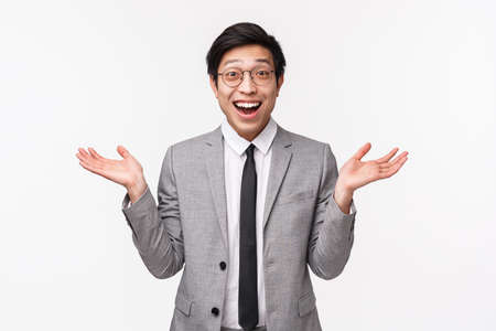 Waist-up portrait of glad and surprised handsome asian male office manager, raise hands sideways amazed and excited, see someone, hear great news and congratulating friend, white background