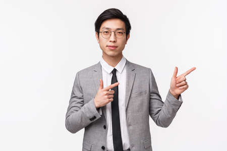 Waist-up portrait of confident, smart handsome asian businessman leading presentation, lecture for office workers, wearing suit, pointing fingers upper right corner and look camera determined