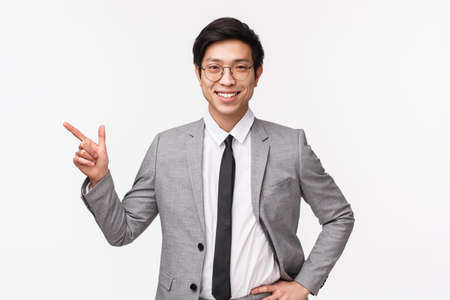 Waist-up portrait of handsome professional male entrepreneur showing new employee office, pointing finger left, look at chat, smiling at camera pleased and proud, standing white background