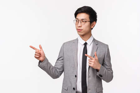 Portrait of determined smart businessman, asian guy in grey suit, looking and pointing left with interest as explain diagram to coworkers at office, presenting project during work, white background